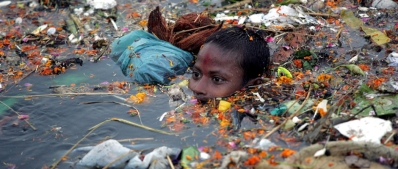 epa00832196 Indian local boy wade through the pollution and floating debris left after the immersion of hundreds of idols of Hindu goddess Durga into the River Yamuna in New Delhi, India Monday 02 October 2006. The Hindu Festival of Durga Puja, celebrates the killing of a demon king by the goddess ended today with colourful celebrations all over the country. Every autumn, Bengalis all over the world celebrate her festival which not only represents the victory of good over evil, but is also a celebration of female power. EPA/HARISH TYAGI